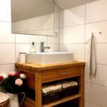 Umyvadlo na dřevěné skříňce, zrcadlo, bílé dlaždičky, květinová výzdoba, ručníky.