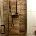 Detail sprchového koutu s dekorem dřeva, sprchová hadice.
