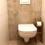 Bílý záchod, dřevěný stojan na toaletní papír, bílé a šedivé kachličky.
