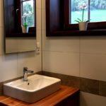 Umyvadlo na dřevěné skříňce, zrcadlo, bílé a kamenná dlaždičky, výhled z okna na louku, na parapetu položená orchidej.