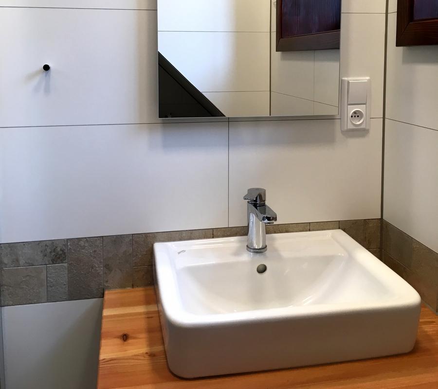 Umyvadlo na dřevěné skříňce, zrcadlo, bílé a kamenná dlaždičky.