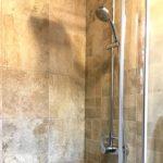 Detail koupelny s dekorem kamene, sprchová hadice.