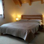Dřevěná manželská postel s šedivohnědým povlečením, noční stolky s lampičkami, květinové závěsy a trámy.