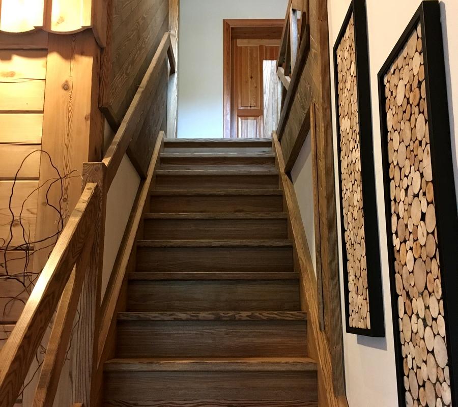 Interiér - Dřevěné schody vedoucí do prvního patra, dekorace ze dřeva, dřevěné trámy.