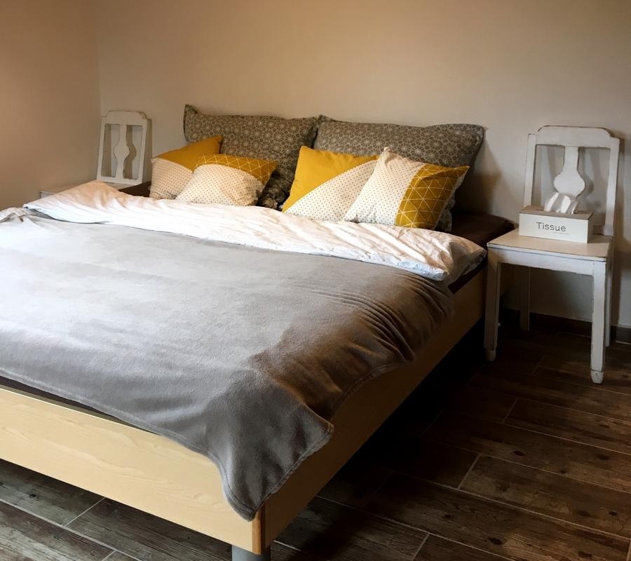 Manželská postel s šedivým povlečením, židle jako noční stolky.