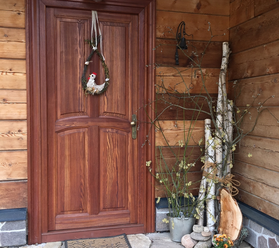 Vchodové dveře s velikonoční výzdobou, dřevěné trámy, břízy, slepička na dveřích, květiny, dekorace.