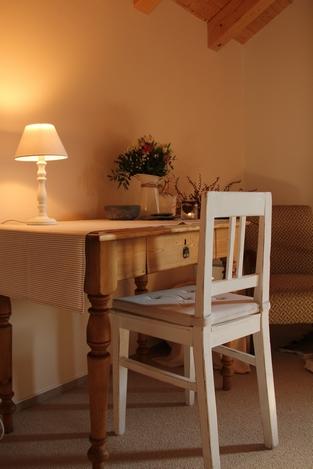 Psací stůl s ubrusem, bílá zrenovovaná židle, květiny na stole, rozsvícená lampička, v dálce hnědé křeslo.