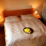 Veliká manželská postel s hnědým povlečením, narcisy na posteli, rozsvícené lampičky, na okraji bílá skříň.