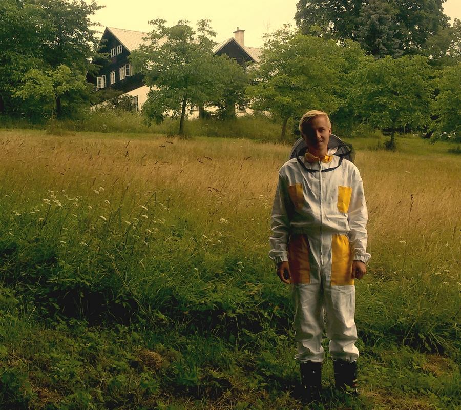 Včelař na louce v bíložlutém obleku , v dálce chalupa.
