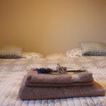 Pohled na béžové ručníky s květinou (levandule) na manželské posteli, zelenobílé povlečení