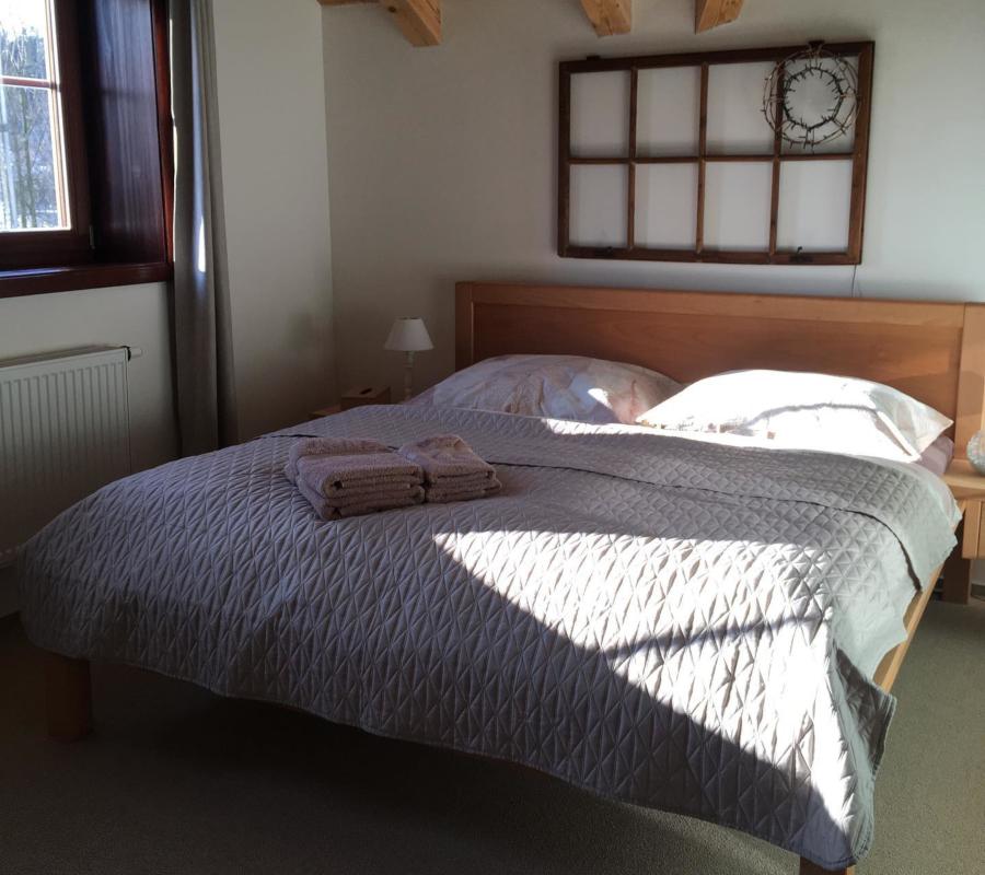 Dřevěná postel s béžovým přehozem a s béžovými ručníky, dřevěné okno jako dekorace na stěně, okrasná lampa.