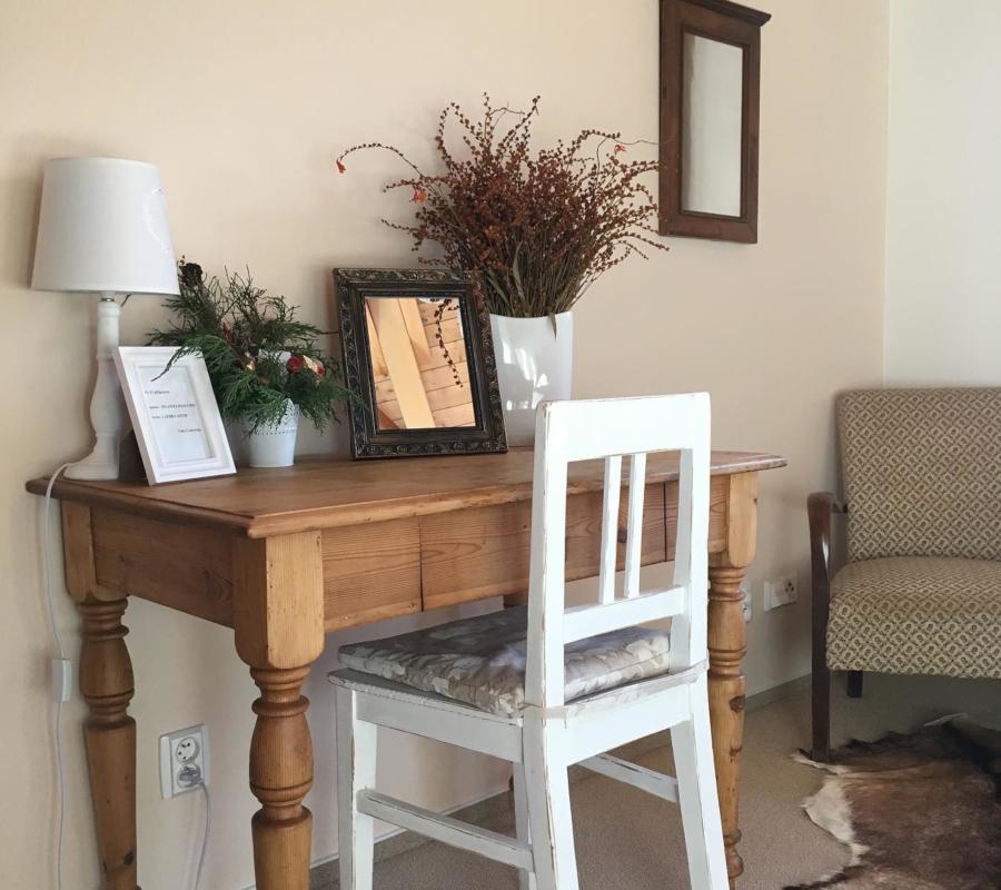 Dřevěný psací stůl, na něm položené zrcadlo, bílá lampička, bílá váza se sušenými květinami, živá dekorace, bílá dřevěná židle a v dálce hnědé zrcadlo, starožitné křeslo a kožešina na zemi.